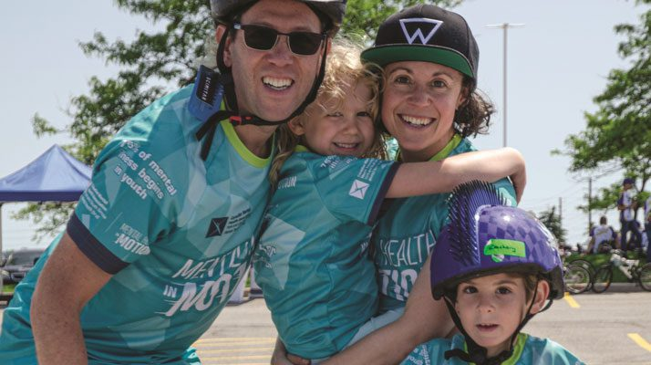 family smiling at a fundraiser with mother holding her daughter and son wearing a helmet