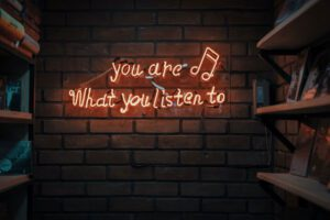 """Lit up neon sign of """"you are what you listen to"""""""