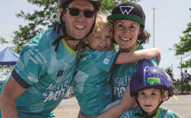 """Family of four: a male, female and two children, smiling for the camera in """"Mental Health in Motion"""" jerseys."""