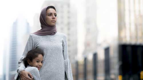 young hijabi mother holding her smiling daughter in her arm