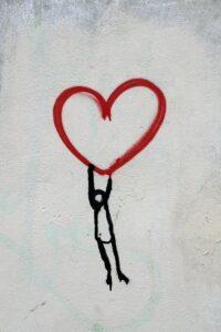 graphic of a black stick figure holding onto a red heart