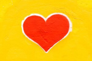 chalk image of a red heart with white outline on a yellow background