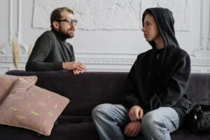 teenage boy sitting on a couch speaking to parent about mental health and suicide