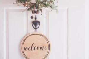 a wooden welcome sign on a white door