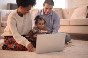 Multi-racial family of three, Mom, Dad and baby, sitting in their living room in front of a laptop.