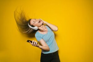 young woman listening to music with headphones on, singing in front of a yellow wall