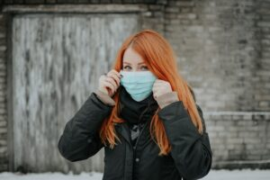 redhead young female holding her mask on her face