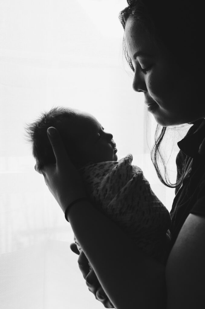 black and white image of mother holding her newborn baby in her hands and looking at him