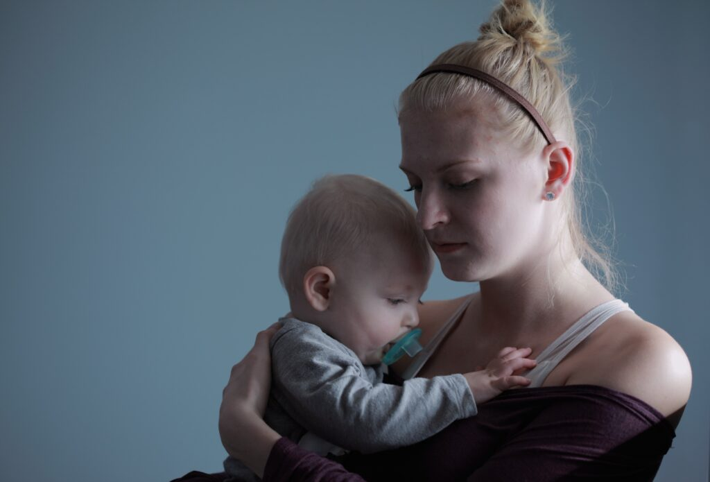 young mother holding her newborn baby in her arms and facing postpartum depression