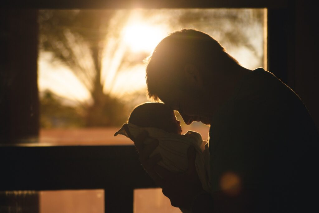 father putting his hand against his newborn baby dealing with postpartum mental health