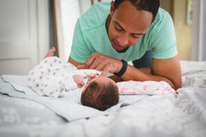 father playing with his newborn baby with postpartum depression