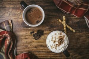 overview of a wooden table with two hot chocolate mugs to represent the holidays