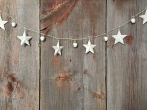 Stars and jingle bells strung together against a fence