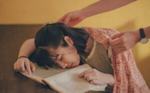 girl sleeping on her book on a table while someone puts a blanket over to help