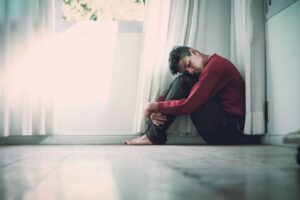 young boy sitting in a corner holding his knees in and sad