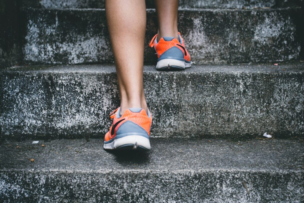 closeup of feet going up steps to represent physical activity to promote self-care