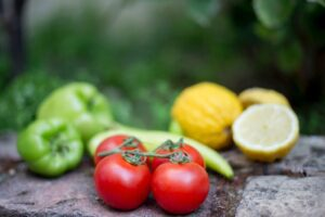 close-up of tomatoes with blurry lemons and green peppers in the back to promote healthy eating