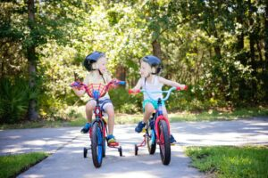 two young girls biking together and smiling at each other