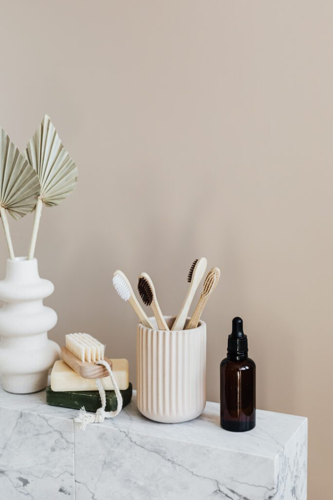 close up of a shelf with bamboo toothbrushes and plant