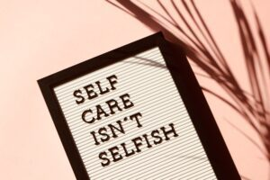 Self care isn't selfish sign with pink background