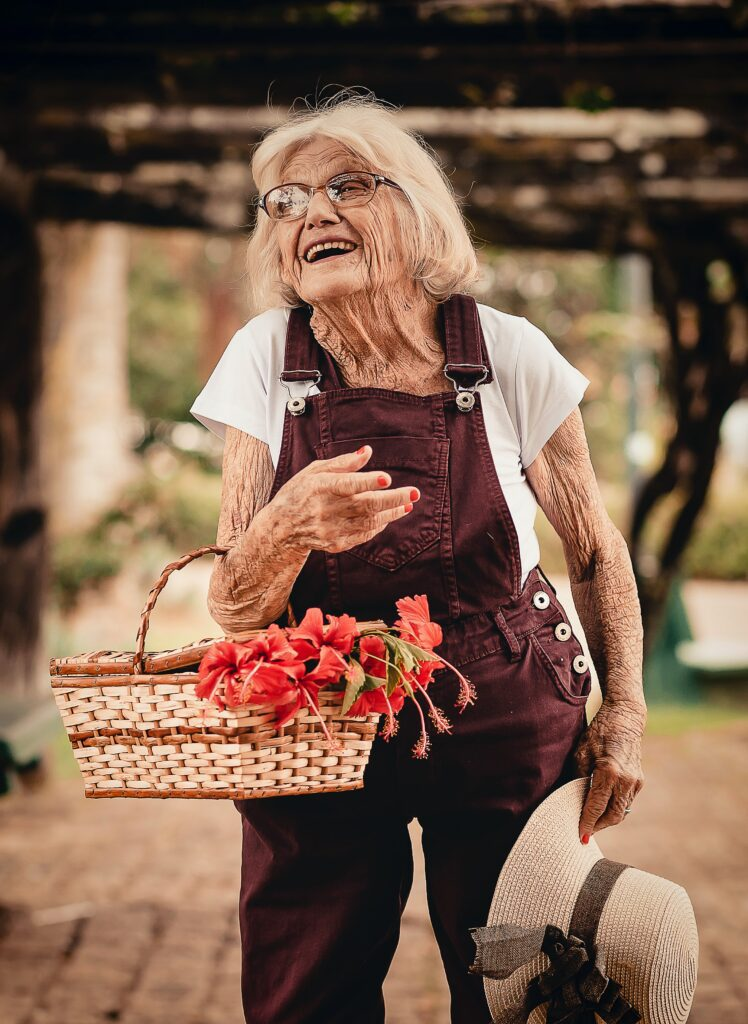 elderly woman carrying flower basket with open smile