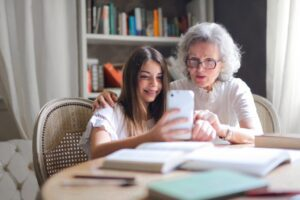 elderly woman with granddaughter looking at a phone together to understand senior mental health