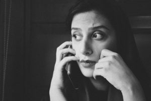 young concerned woman with phone against her ear for telephone-based supportive counselling