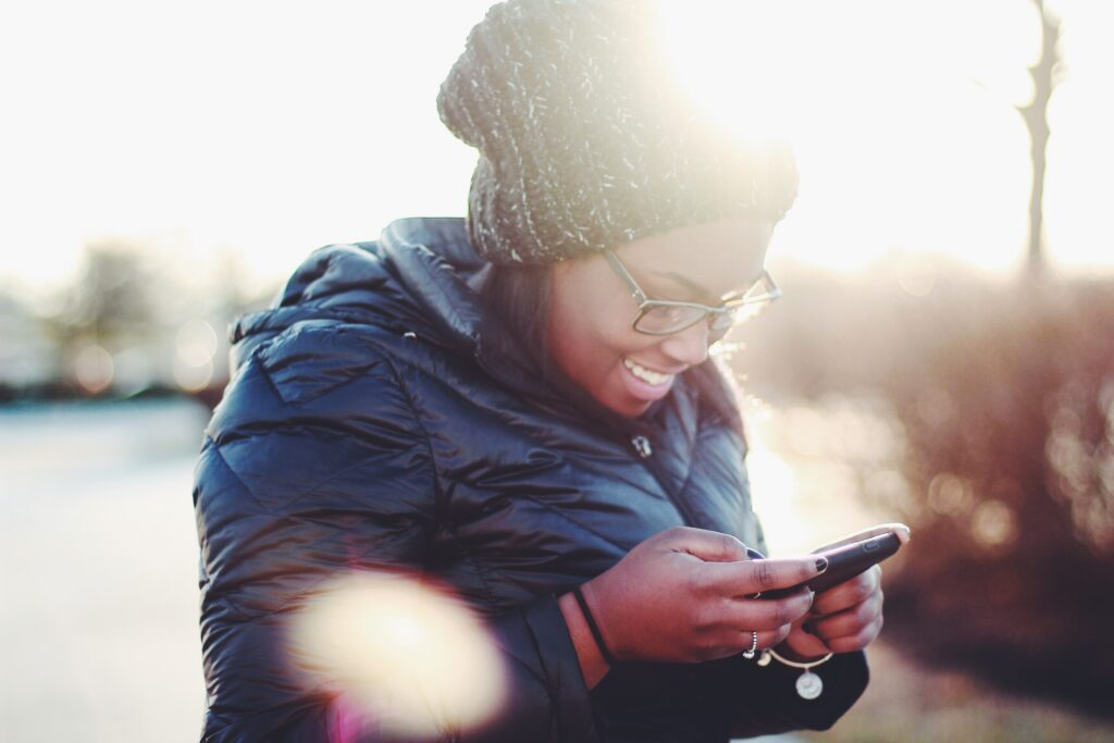 young woman smiling at her smartphone