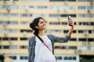 young brown woman taking a selfie from her smartphone outside
