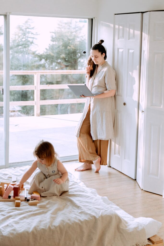 mother standing with laptop in her hand and her child is playing on the bed