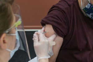 closeup of COVID-19 vaccine injected in a man's arm