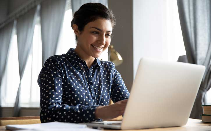 Woman looking at laptop, with large smile on her face