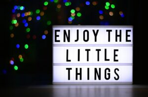 sign of enjoy the little things with colourful lights in the background