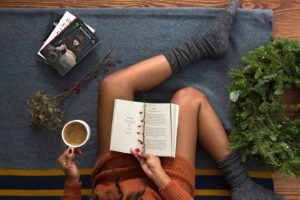 Overview shot of a woman with an open book in her lap and a mug of coffee in her hand practicing self-care during the holidays