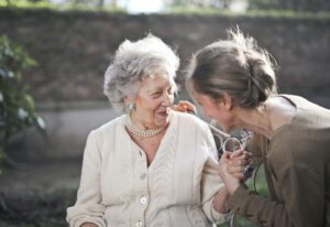 Two adult woman talking to each other outside