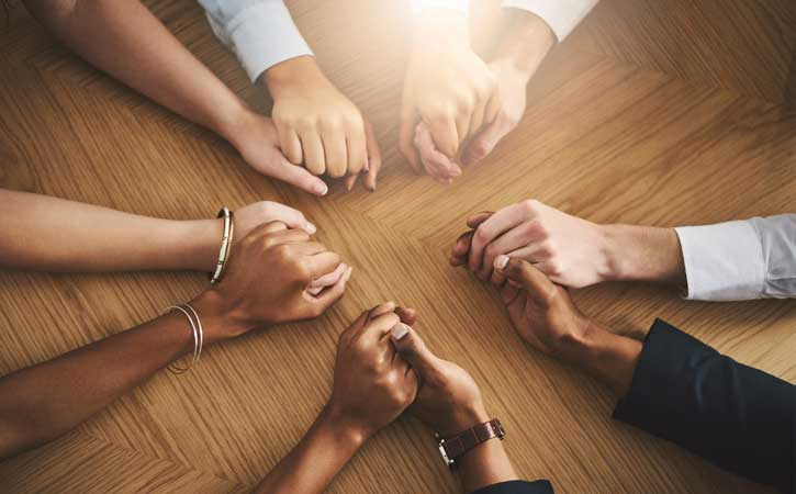 diverse groups of two holding one another hands