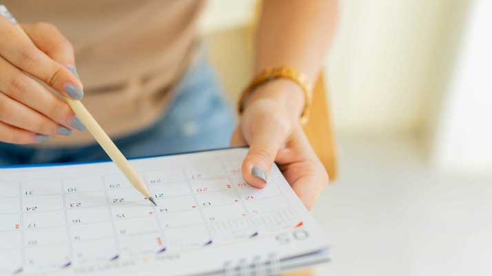 Close-up image of hands with painted nails holding a pencil and a calendar