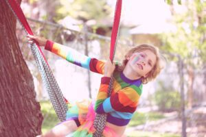 Young child playing outside with rainbow face paint and clothes