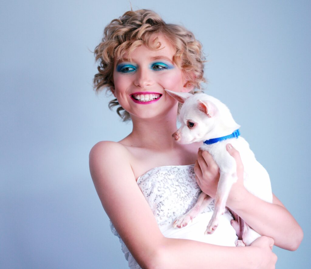 young child holding a dog with makeup on face to represent trans, non-binary or gender non-conforming