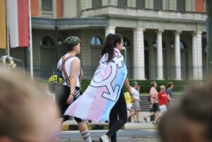 woman wearing a cape with trans, non-binary and gender non-conforming sign