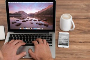 hands hovering over a laptop screen with smartphone and mug next to it