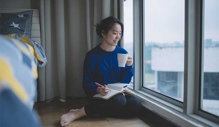 woman sitting by her windowsill with coffee and journal in her hand