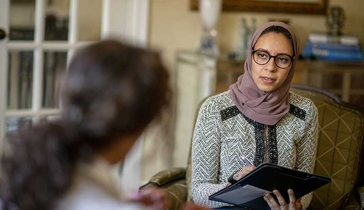 young hijabi mental health specialist discussing with young woman