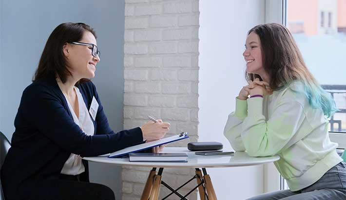 Woman wearing badge sitting on left of a small table and holding a clip board. Across from her is young woman with blue in her hair smiling back at first woman.
