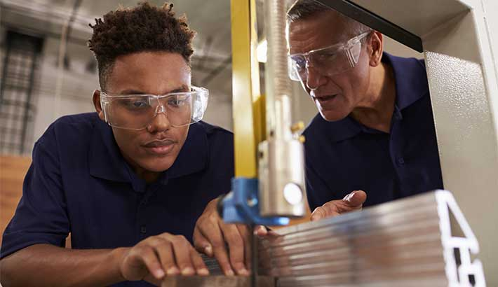 Young adult black male using equipment and wearing goggles with an older man guiding him who is also wearing goggles.