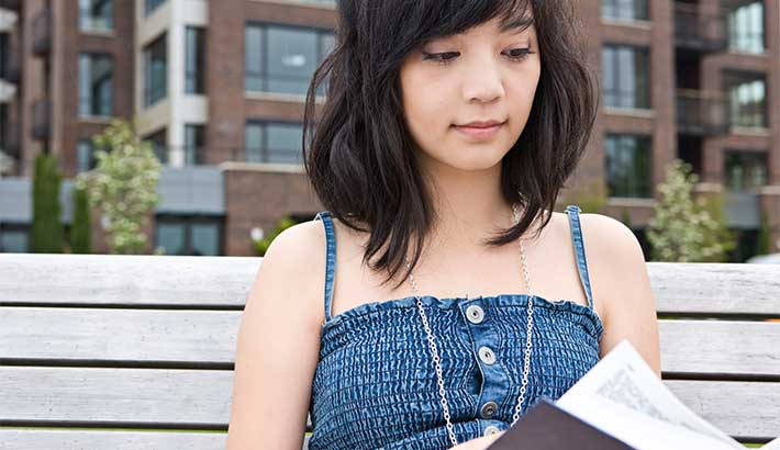 Close-up of young adult woman sitting on a bench reading a book, buildings in the background.