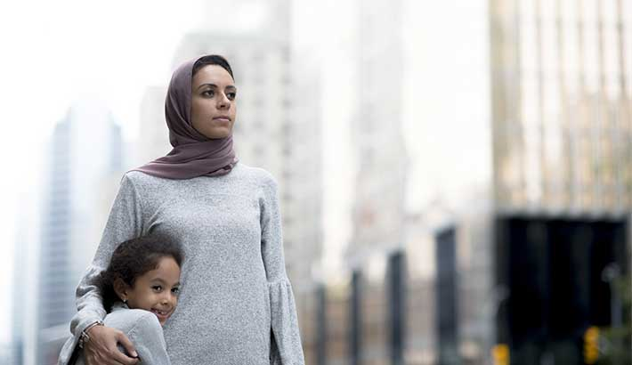 Woman standing outdoors in a city landscape and wearing a hijab. Her arm is around a young girl who is hugging her side. The background is blurred.