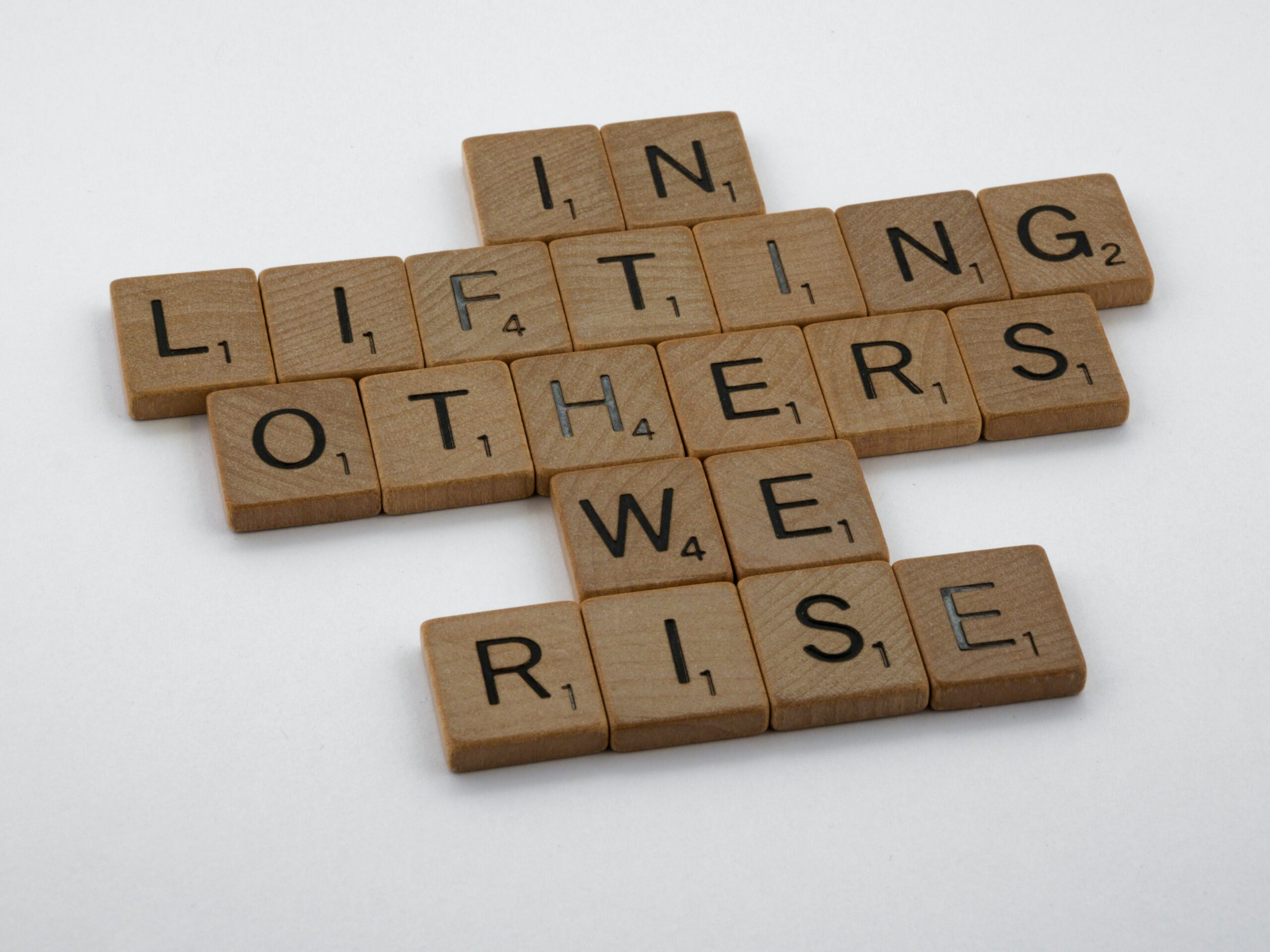 Scrabble tiles spelling out 'In lifting others we rise' against white background