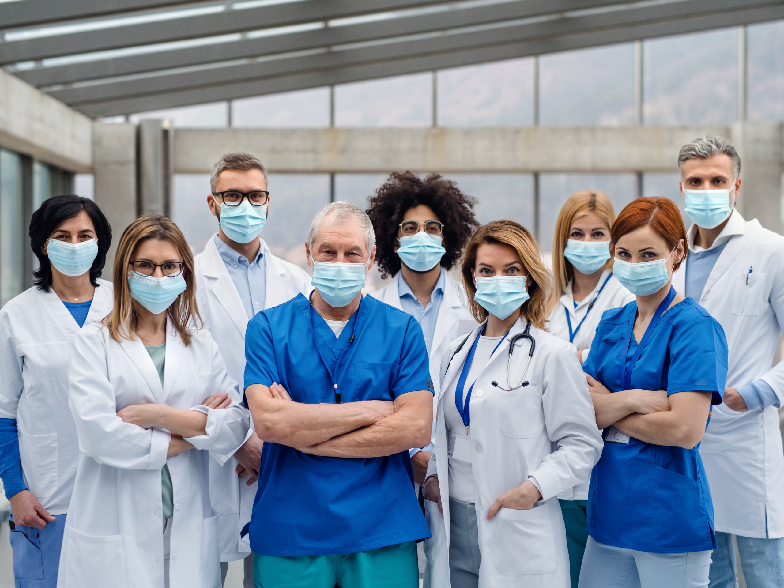 A group of nurses and doctors standing together with mask on