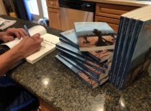 """Aaron Hanania autographing copies of his new book :The Kings Pawn"""" for fans this week."""